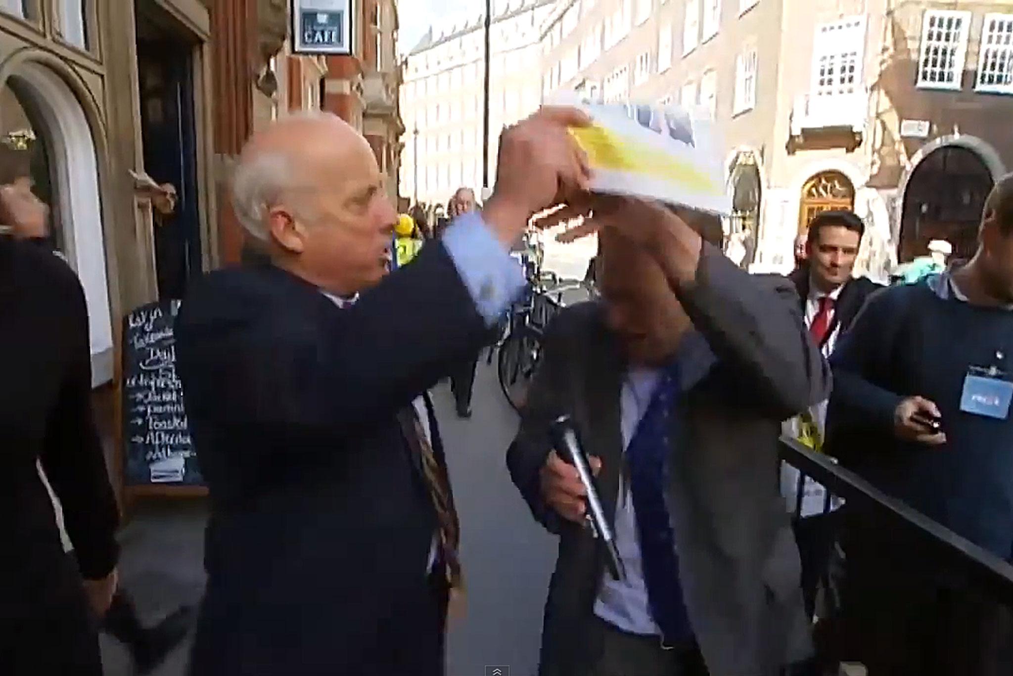 Godfrey Bloom hits Michael Crick over the head with a UKIP brochure.