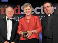 Helen Baker accepting her award from Richard Lane, acting manager at Ansvar [l] and host Rev Richard Coles