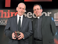 Host Reverend Richard Coles [r] hands the award to Dennis Rogers, a volunteer at Thames Reach