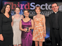 Imogen Ward, director of marketing and communications at Merlin, holds the award, with colleagues [l to r] Kate Turner, head of communications and campaigns, Freya Tringham, communications officer, and Kylie Harrison, media officer, with host Reverend Richard Coles