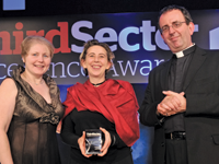 Elephant Family trustee Lorin Gresser picks up the award [c] from BT MyDonate general manager Donna Young and host Reverend Richard Coles
