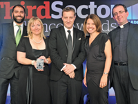 [from left] Michael Naidu, acting chair of the PFRA, gives the award to Catherine Johnstone, chief executive of Samaritans, Martin Gallagher, head of level crossings at Network Rail, and Rachel Kirby-Rider, director of fundraising at Samaritans, with host Rev Richard Coles