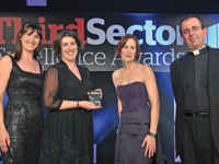 Beth Pedersen [l], publisher of Third Sector, presents the award to Jenny Perez [centre], director of Eric, and Natasha Collins-Daniel, education and media coordinator at the charity with Reverend Richard Coles
