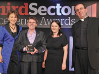 Dame Suzi Leather [l], chair of the Charity Commission, presents the award to Megan Stewart, reconnections manager at Thames Reach, and her colleague Audrey Mitchell, director of street and hostel services with presenter Reverend Richard Coles