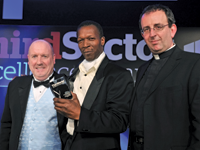 BarringtonWright [c] receiving his award from Andy Partington, UK sales manager at Markel [l], with host Rev Richard Coles
