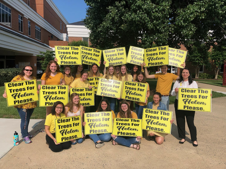 image of students holding signs that say clear the trees for helen please