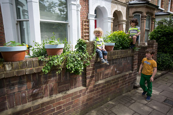 three children in front of house with plant pots