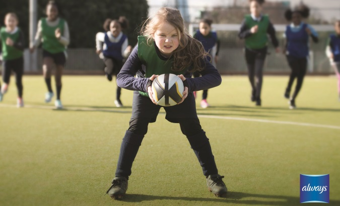 young girl holding a soccer ball on the field