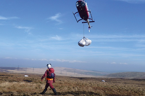 Helicopter dropping off bas of heather brash