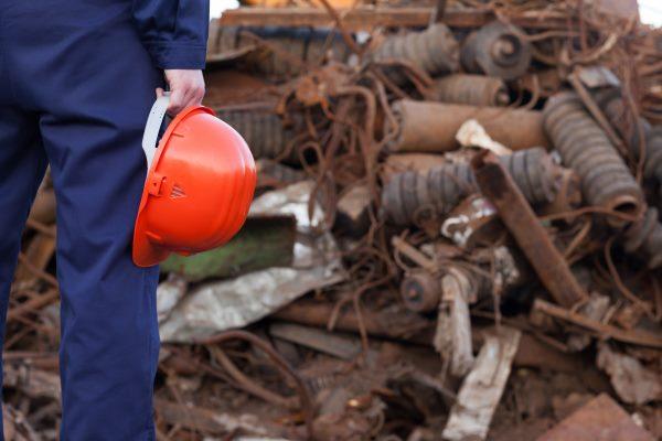 Worker holding helmet, scrap pile