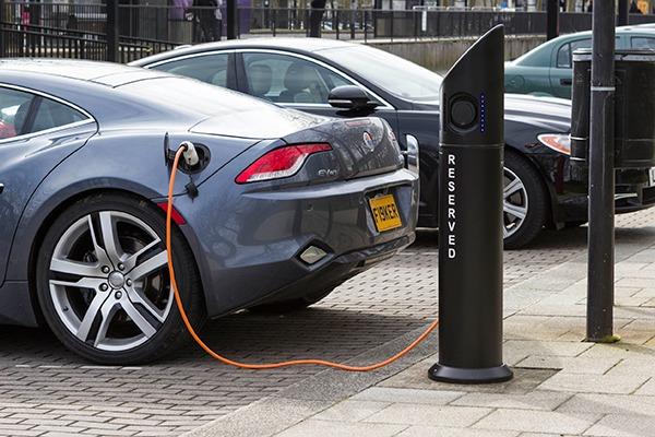 Modern electric car charging at station dock point near parking lot, United Kingdom . Photograph: Olga Marc/123RF