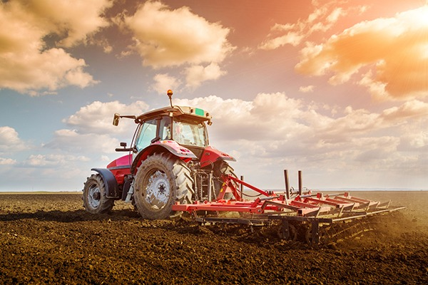 Tractor ploughing field, farmland soil