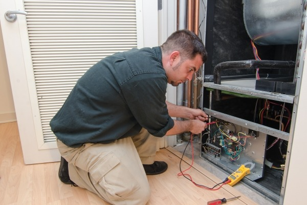 Technician working on an air conditioning system using F-gas