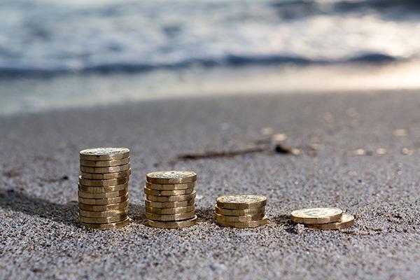 Row of pound coins piled on beach. Photograph: Daniel Kaim/123RF