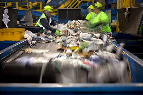 People sorting waste from conveyor at recycling facility. Photograph: Huguette Roe/123RF