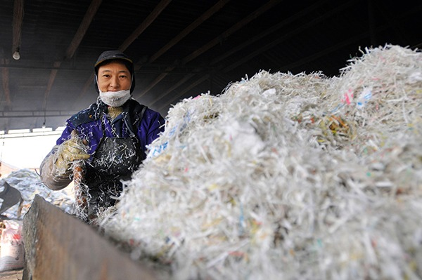 Chinese man processing shredded plastic. Photograph: CPress Photo Limited/Alamy Stock Photo