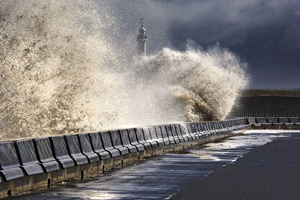 Wave crashing onto coastal road. Photograph: Designpics/123RF