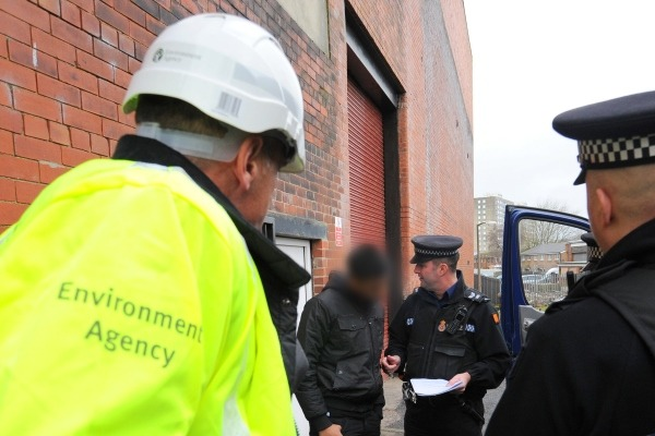Environment Agency officer looks on while the police arrest a waste criminal