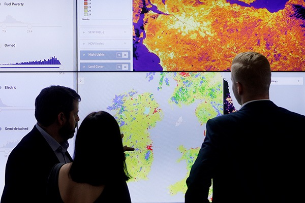 People looking at heat maps on a large screen