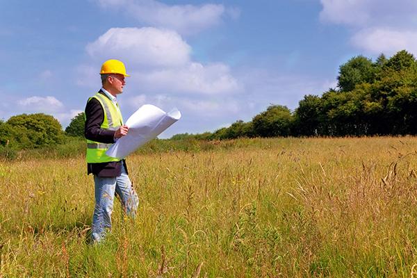 Man in hi-vis jacket and helmet standing in field holding plans