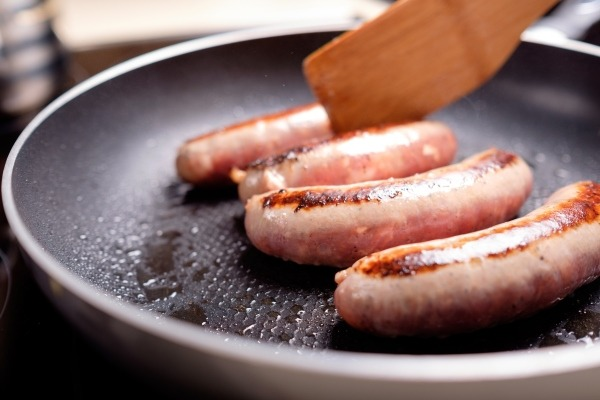 Sausages cooking in non-stick pan