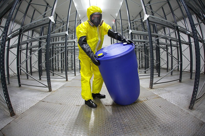 Man in personal protection clothing handling a chemical drum