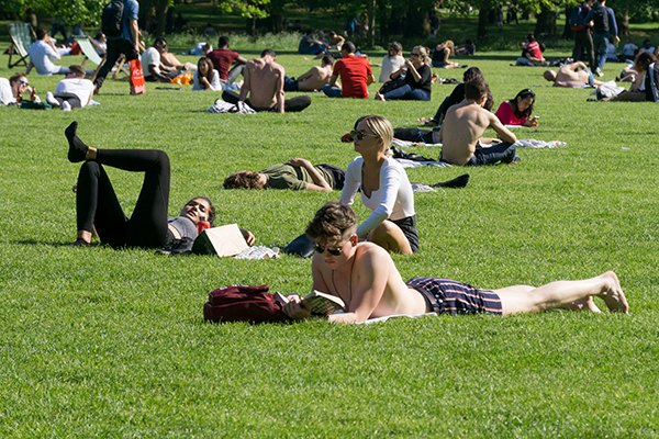 People sitting in a London park enjoying the sun