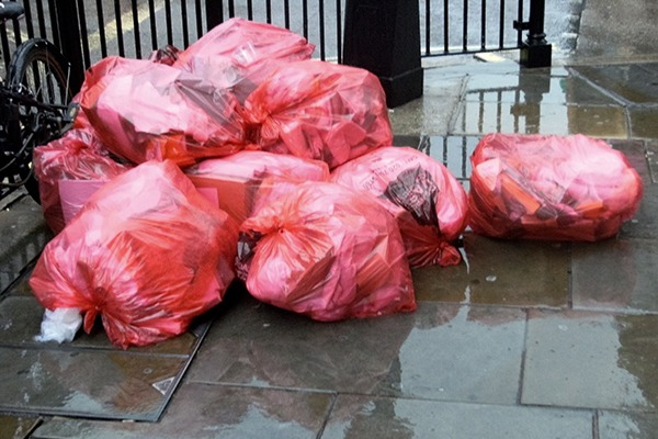 Bags of commercial waste on pavement