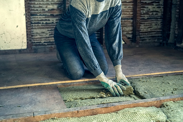 Woman insulating a loft