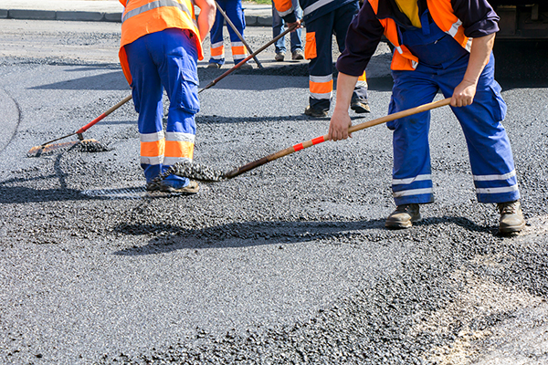 Workers repairing road surface