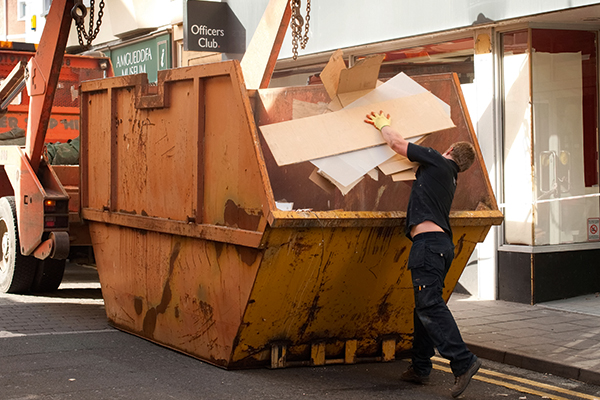 Man putting waste into a skip