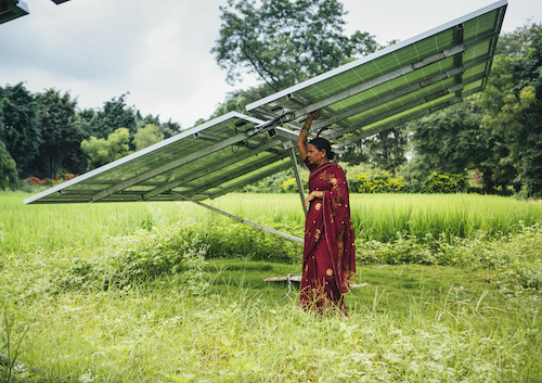 woman standing beneath a solar panel